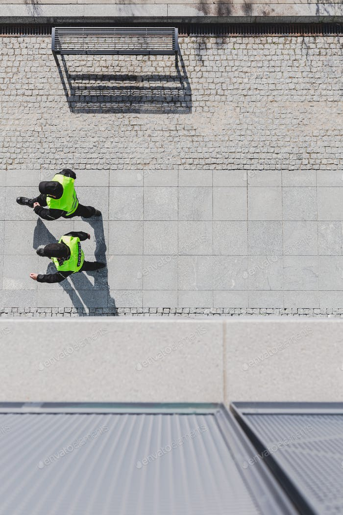 Top view of two cops patrolling city streets wearing black uniforms and vests