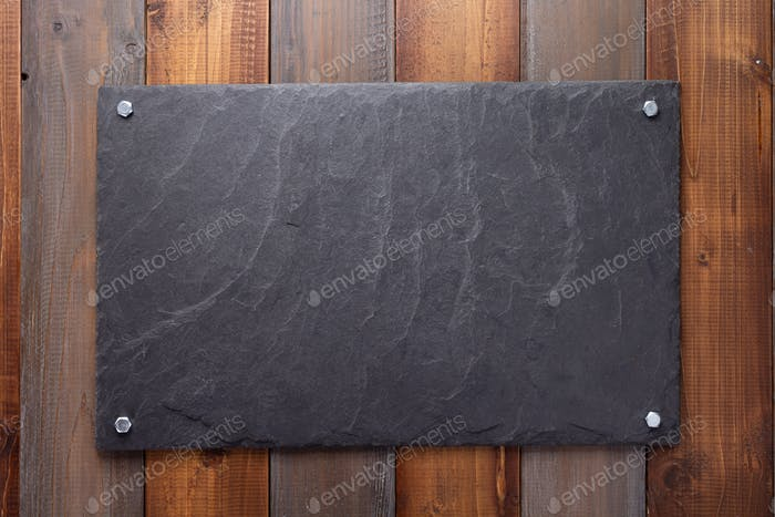 black slate stone at wooden background