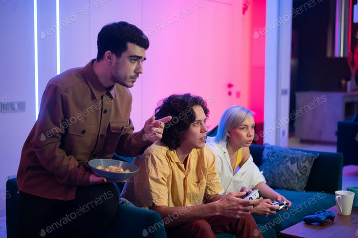 Happy young people playing video games on console while sitting on couch in front of tv. Man advice