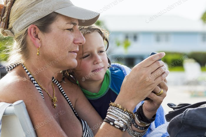 mother and 5 year old son looking at smart phone at the beach