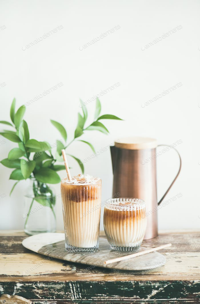 Iced coffee drink in tall glasses with milk, vertical composition
