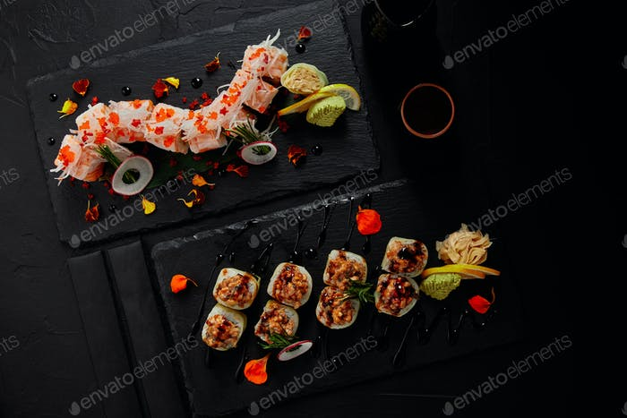 top view of delicious fresh sushi rolls on slate boards and chopsticks