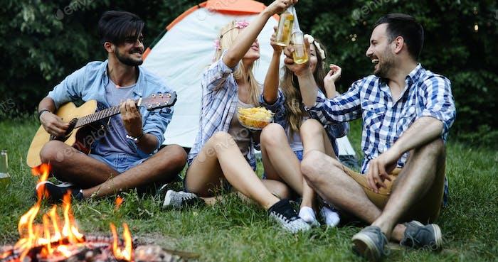 Freunde genießen Musik in der Nähe des Lagerfeuers