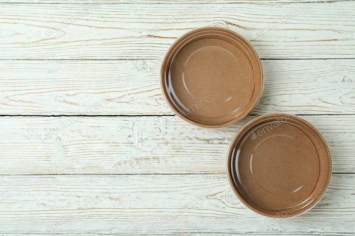 Empty paper bowls on white wooden table