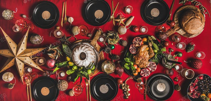 Flat-lay of festive table with roasted turkey, fruits and decorations