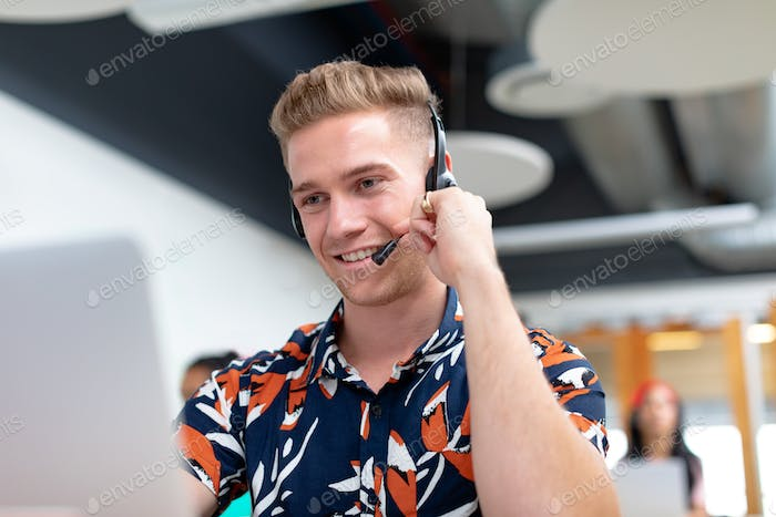 Front view of happy Caucasian male customer service executive talking on headset in a modern office