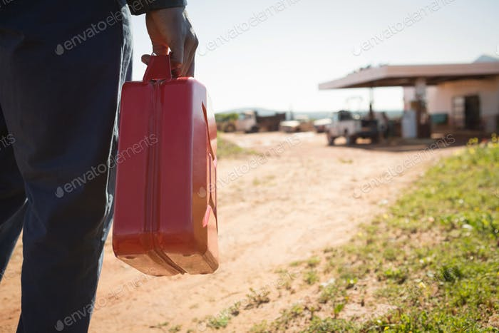 Man walking with a petrol can on a sunny day
