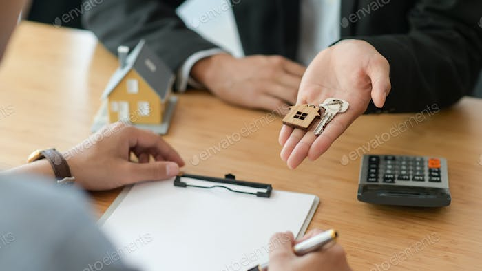 Cropped shot of signing a home purchase contract while the broker holds the house key.