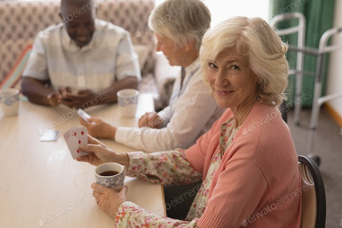 Front view of senior woman playing cards with senior people around table in living room at home