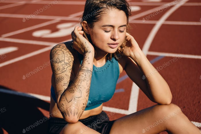 Attractive athlete girl in wet sportswear dreamily resting after workout on city stadium