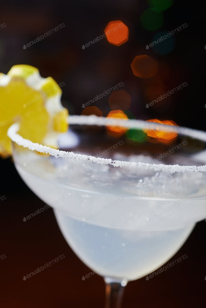 bright beautiful glass of alcoholic cocktail or lemonade on a table in a bar. soft focus.