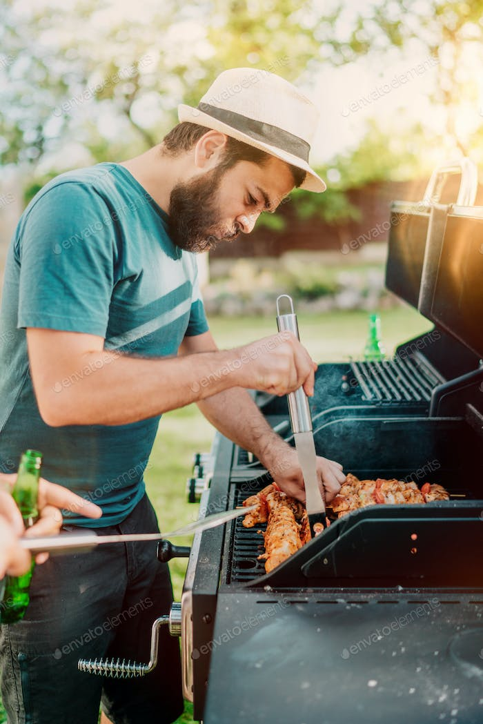 Bearded man grilling chicken at barbecue party