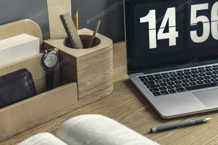 Close-up of wooden desk organizer with pencil and watch, compute