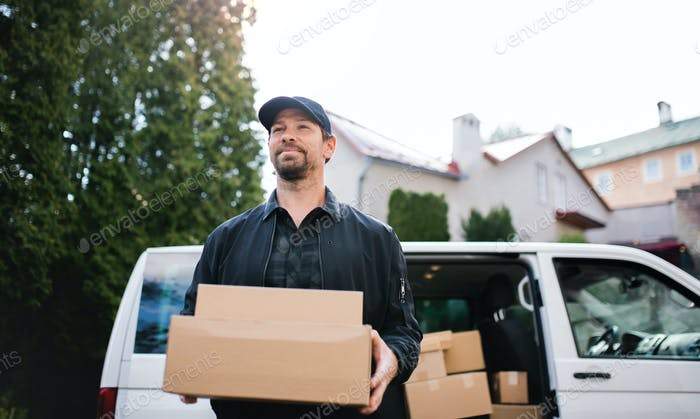 Portrait of delivery man courier delivering parcel box in town