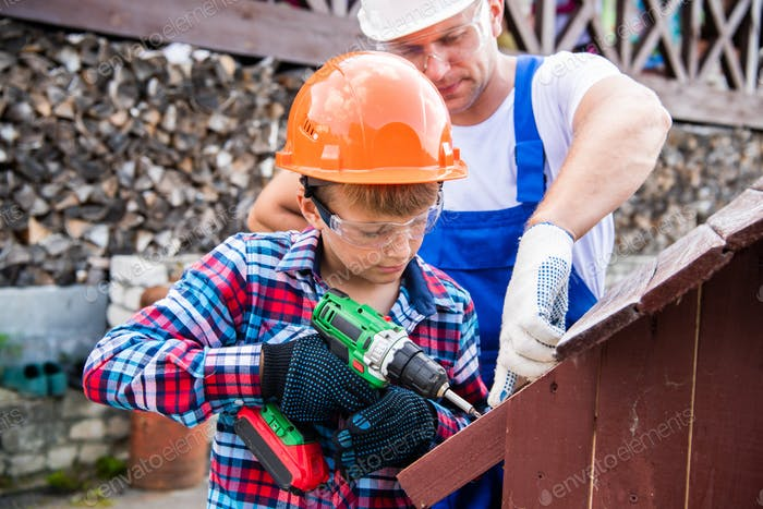 Father and son are building a doghouse together. Father is teaching his son to use the electric