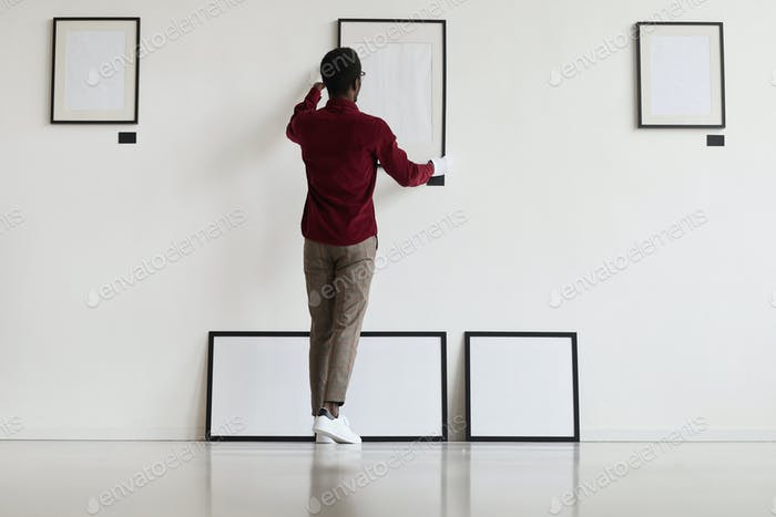 African Man Setting Up Frames in Museum