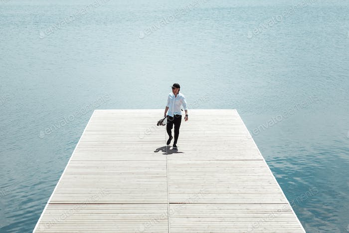 Photo of modern man with electric scooter at a wooden pier