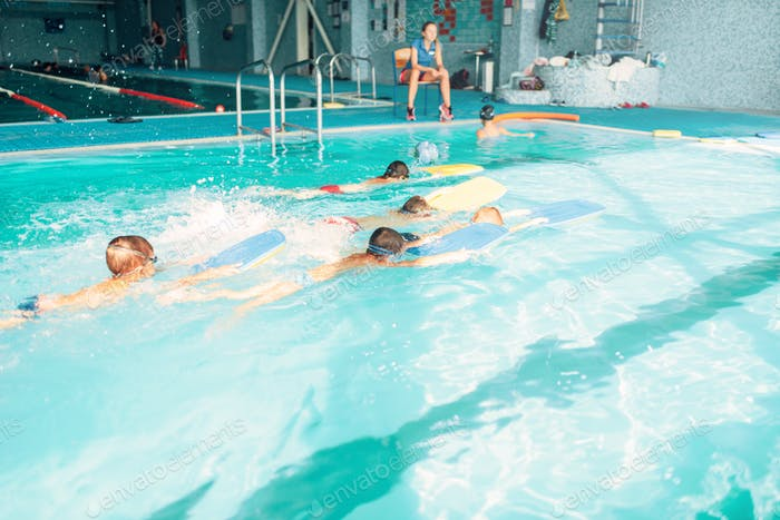 Boys swimming with plank in a pool race
