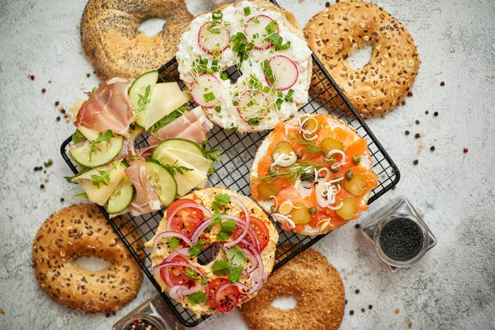 Delicious Bagel sandwiches with creamy cheese, ham, hummus, salmon and vegetables