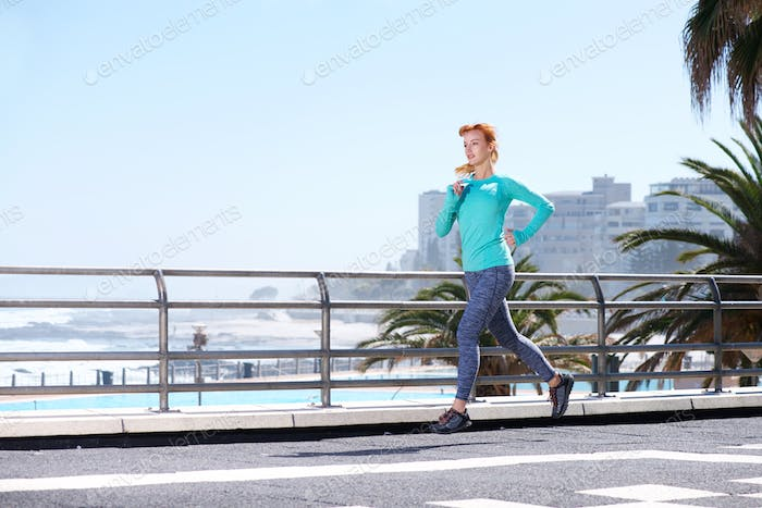 attractive runner training on path outdoors by sea