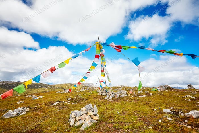 Buddhist prayer flags on the top of a mountain.