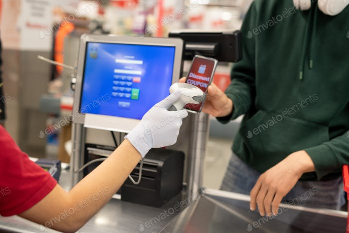 Guy in casualwear holding smartphone with discount coupon on screen by scanner