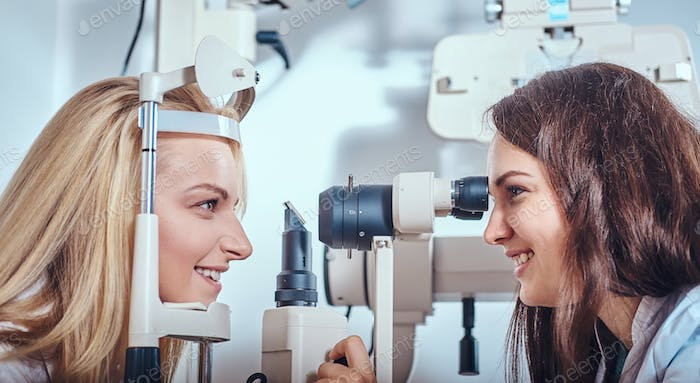 Woman Is checking her sight at optician cabinet
