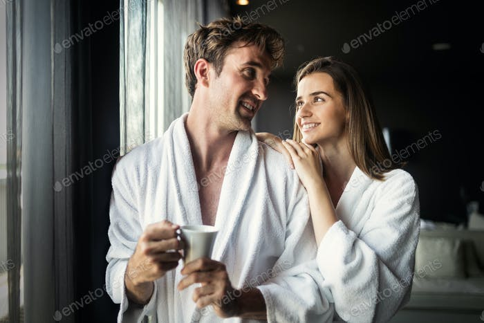 Happy couple in white bathrobes drinking coffee together at morning