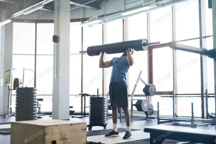African-American Man Lifting Weights in Gym