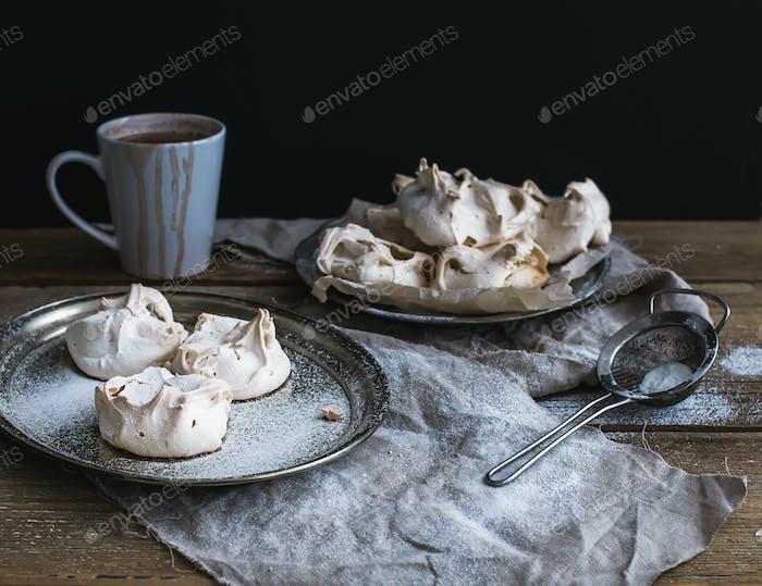 Weißer Baiser und Becher heißer Schokolade auf einem rustikalen Holztisch. Schwarzer Backdro