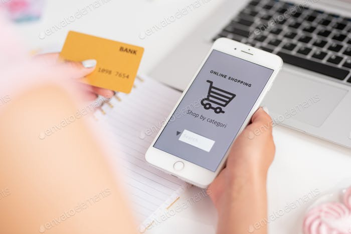 Young consumer of online shop with smartphone and banking card searching goods