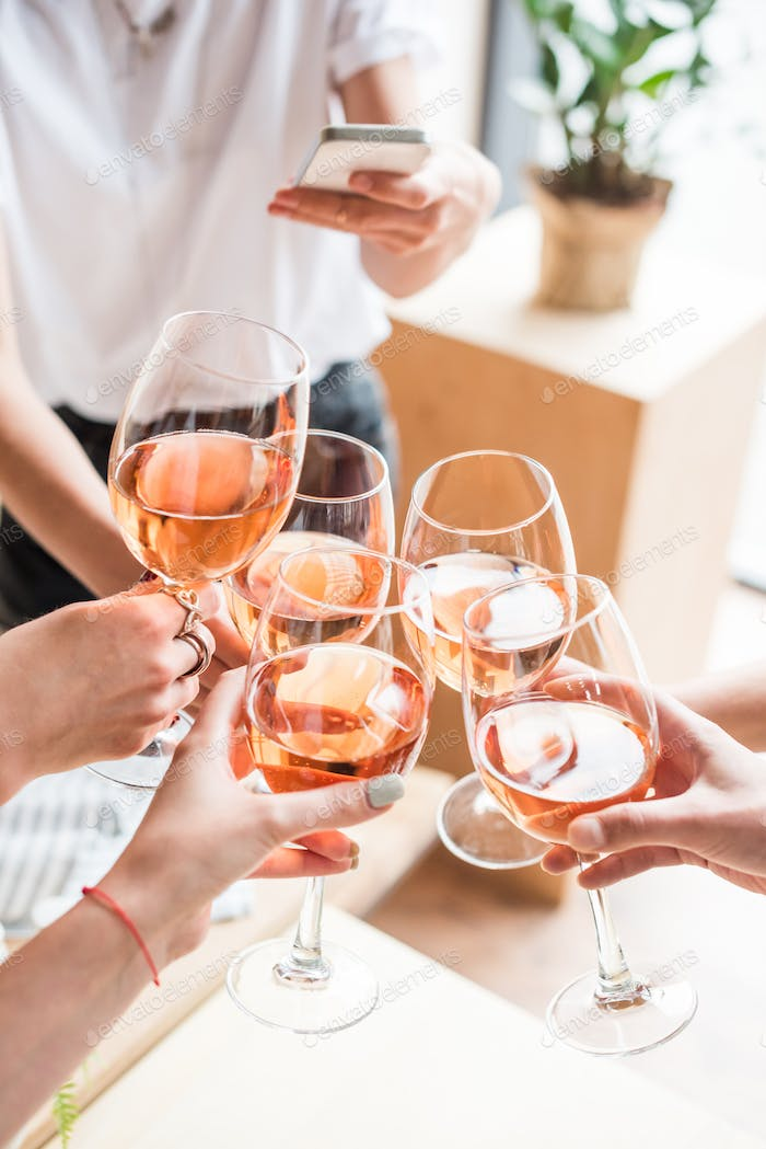 cropped view of women clinking with wineglasses with pink wine