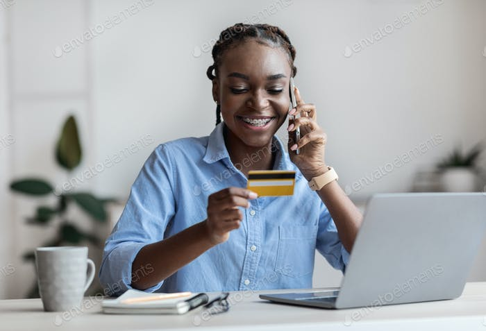 Mobile Payments. Businesswoman Holding Credit Card And Talking On Cellphone In Office
