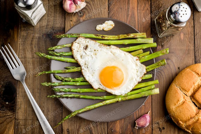 aerial shot of a plate with fried egg and asparagus on barbecue on rustic wood