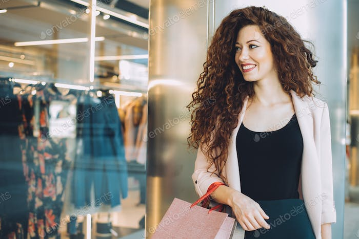 Happy beautiful young redhead woman doing shopping