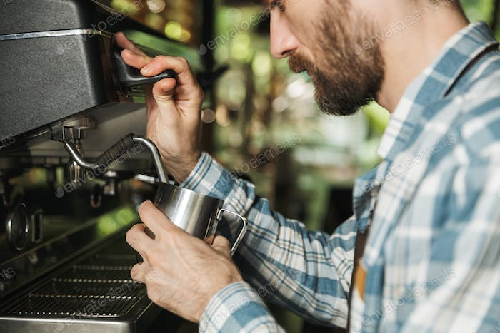 Image of bearded barista man making coffee while working in cafe
