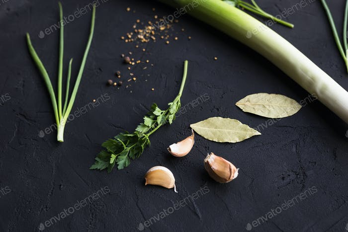 Fresh leek and garlic on a black background