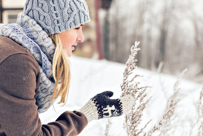 Attractive young woman in wintertime outdoor. Snow and cold
