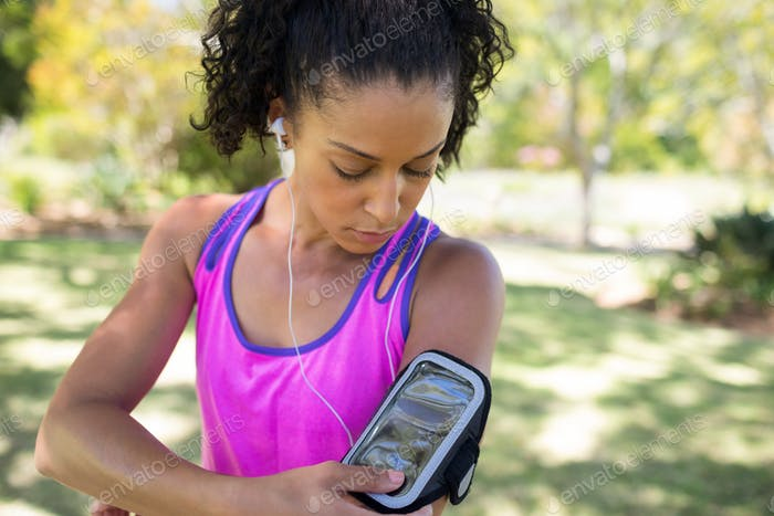 Jogger woman touching the mp3 player in armband