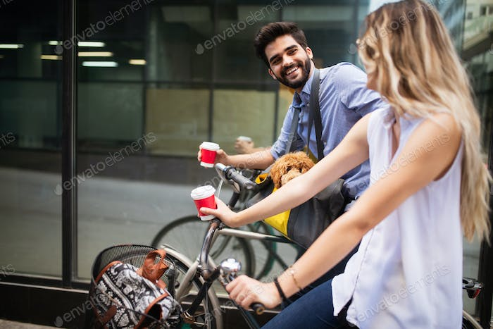 Beautiful young couple on a bike ride on a sunny day in the city