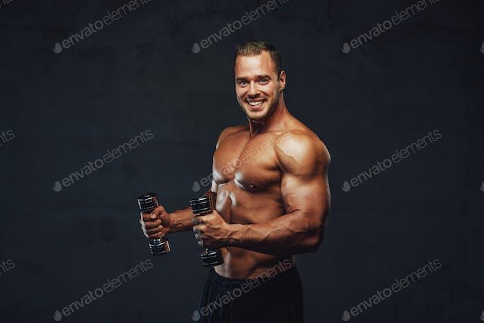 Schöner brutaler Bodybuilder posiert mit Hanteln