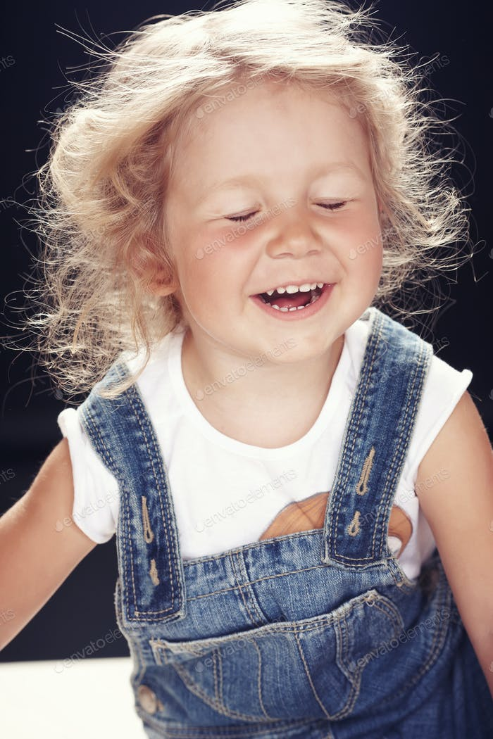Porträt eines glücklichen niedlichen kleinen Mädchens in Denim-Overalls, sitzt in einem Studio auf schwarzem Hintergrund.
