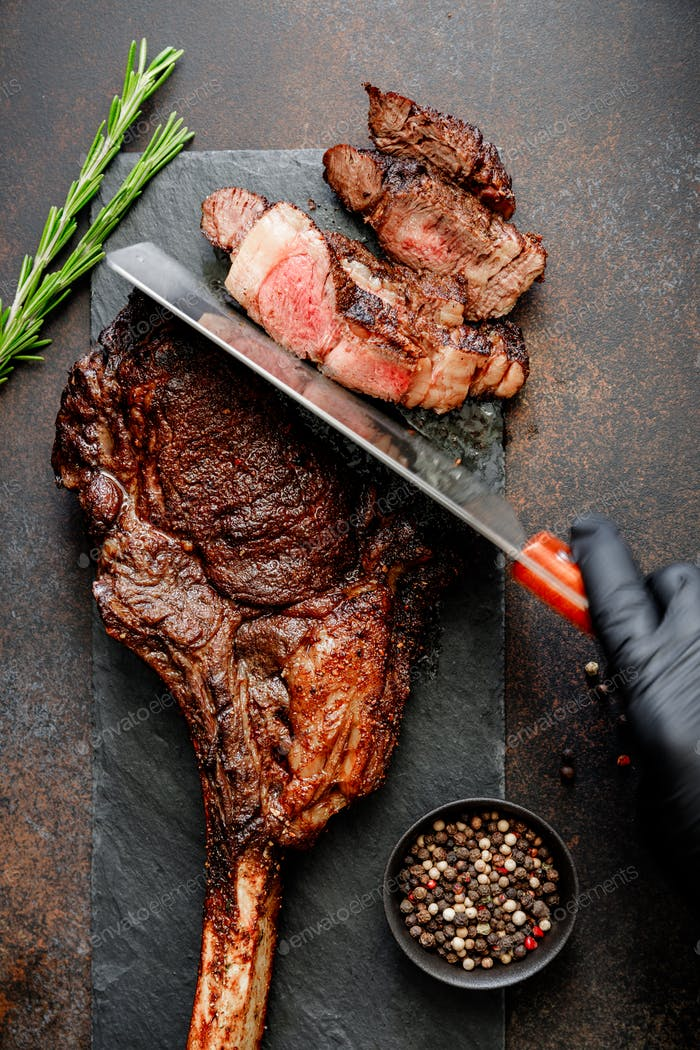 Hand in black gloves cuts dry-aged marble beef steak Tomahawk