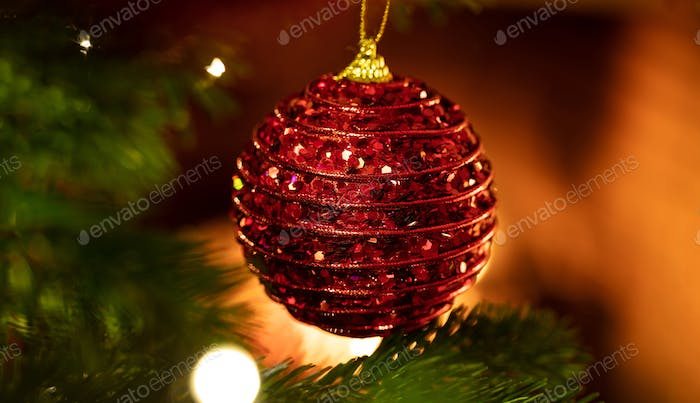 Christmas bauble hanging on a spruce, closeup view