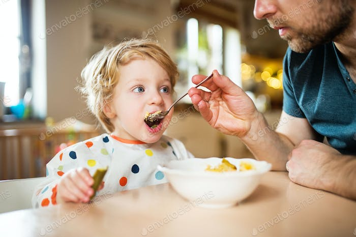 Father feeding a toddler boy at home.