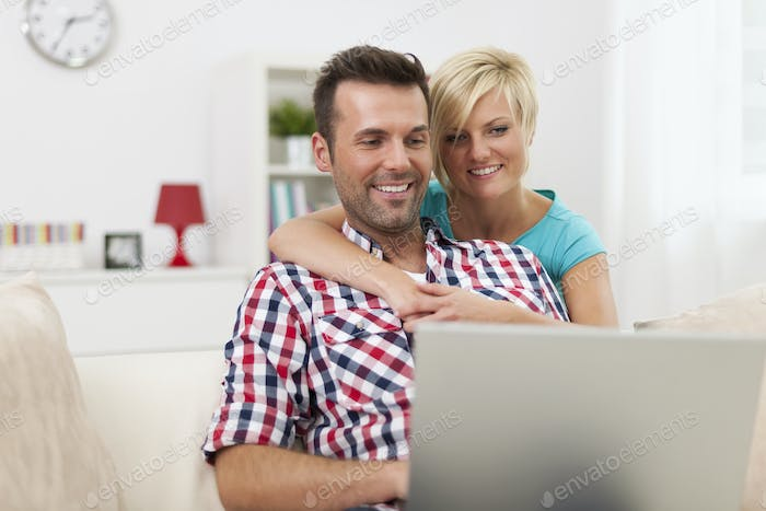Happy couple sitting in living room and using laptop