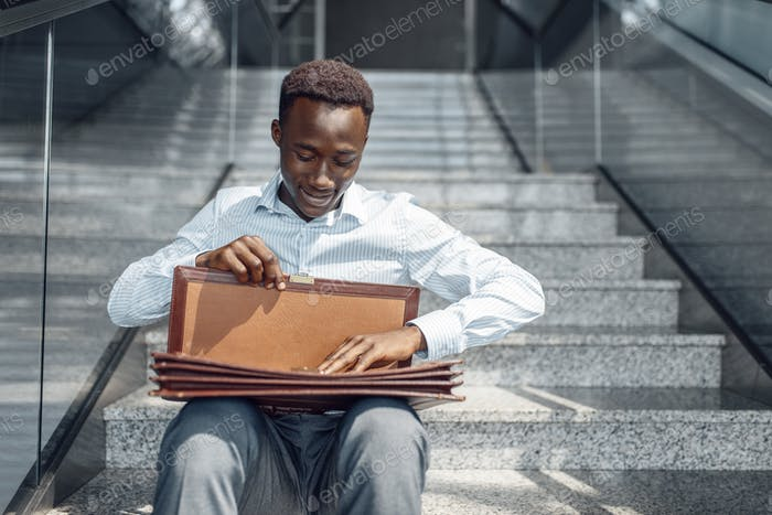 A businessman with briefcase sitting on stairs