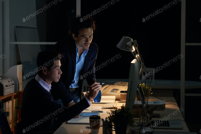 Asian businessmen working in dark office