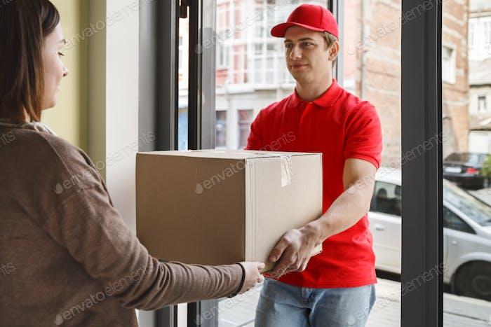 Kauf im Online-Shop und Lieferung. Mädchen nimmt Pappschachtel vom Kurier