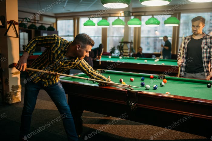 Two male billiard players spend time in poolroom